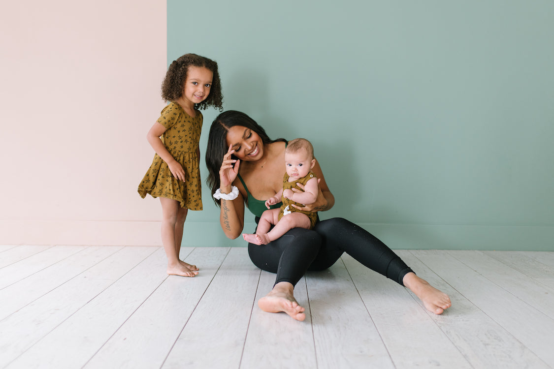 Mother sitting on floor with toddler girl and infant