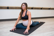 Crow pose in the yoga studio in blush pink maternity belly band