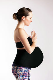 Pregnant woman with prayer hands wearing black belly band