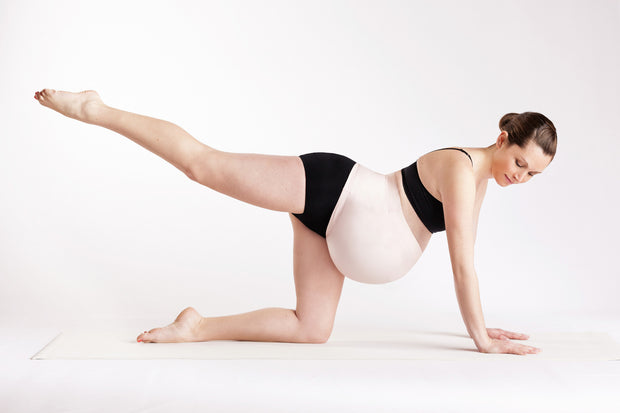 Yoga pose pregnant woman in blush pink support band