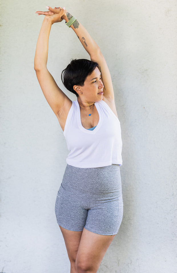 Woman side stretching in white crop tank top and gray shorts