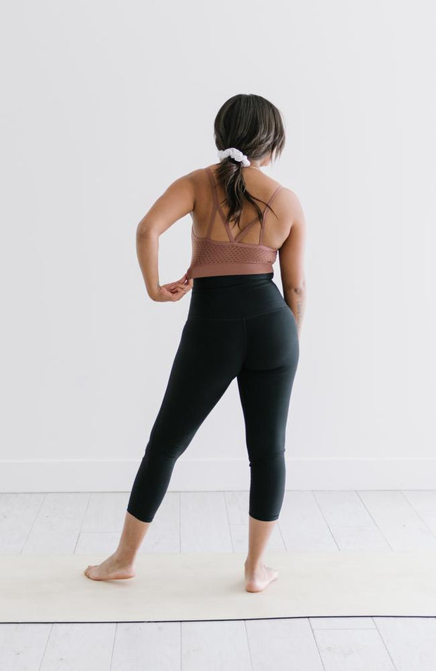 Back of woman standing on yoga mat wearing black crop leggings