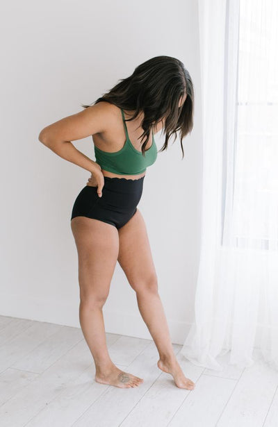 Woman standing in front of window wearing high waisted black underwear and green bralette