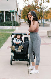 mom pushing stroller with toddler on sidewalk
