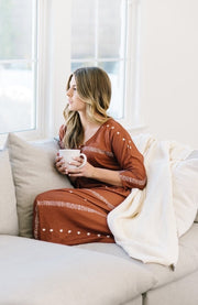 Woman lounging in flowy brown dress with coffee on sofa