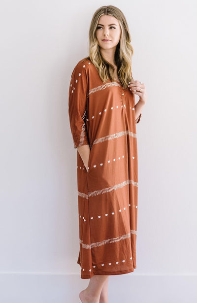 Woman standing in copper midi flowy dress