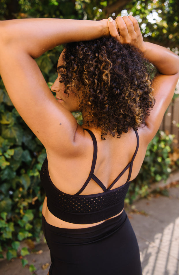 back of woman stretching in sports bra