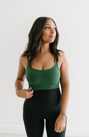 woman in green bralette and black yoga pants