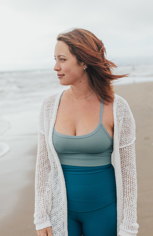 Woman in light blue bra and leggings standing on beach