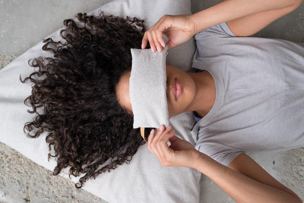 Woman lying down with eye pillow over eyes