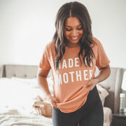 Brunette wearing peach Made to Mother tshirt