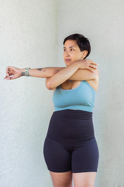 Woman stretching arm across body in light blue sports bra and black shorts