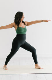 Woman doing yoga in black leggings and green sports bra