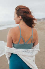 Woman in light blue strappy bra and white shawl on beach