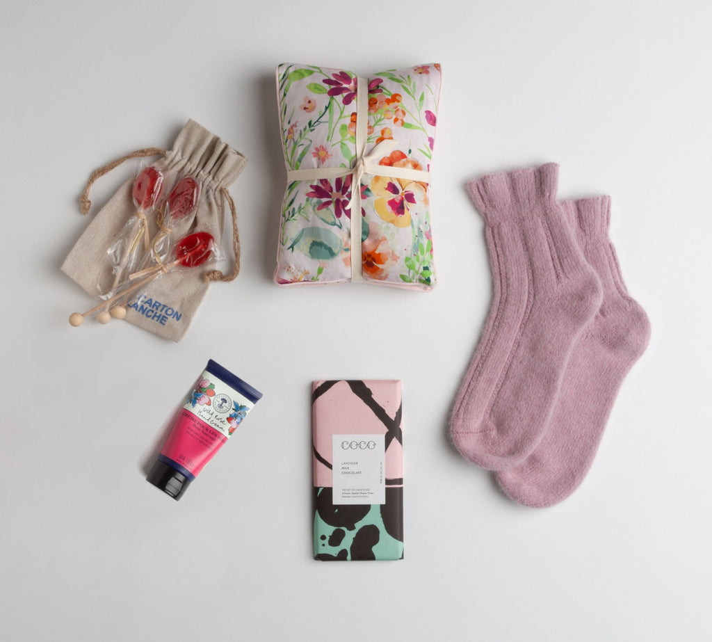 floral heat pillow, rosy pink angora bed socks, lavender milk chocolate bar, wild rose hand cream by Neal's Yard Remedies and floral print heat pillow in pinks and yellows combine for a perfect get well gift.