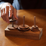 Towers of Hanoi:  Handsome wooden version of the logic game that has been challenging players since 1883. The object is to move the disks from one tower to the other without placing a larger disk onto a smaller one. Made out of eco-friendly monkey pod wood.