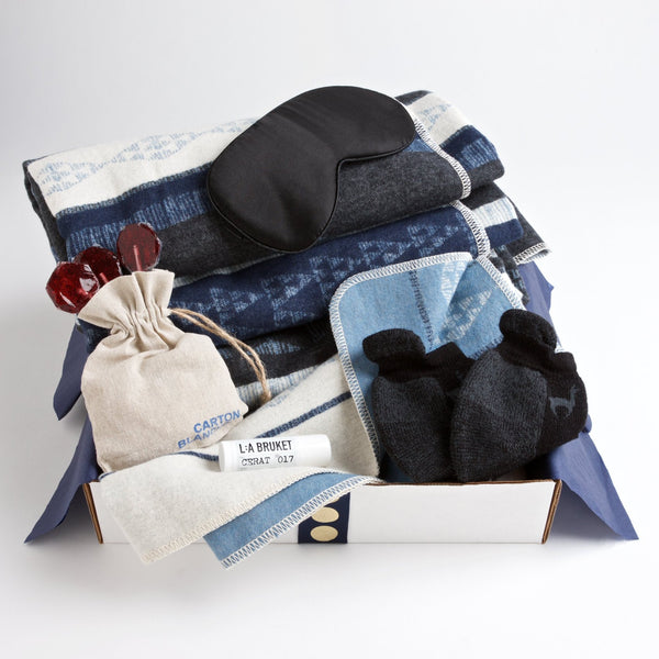 Carton Night Sky - this get well care package includes a modern, reversible throw from David Fussenegger in rich shades of grey and navy, as well as an ebony eye mask, alpaca non-slip socks, soothing lip balm and organic lollipops.