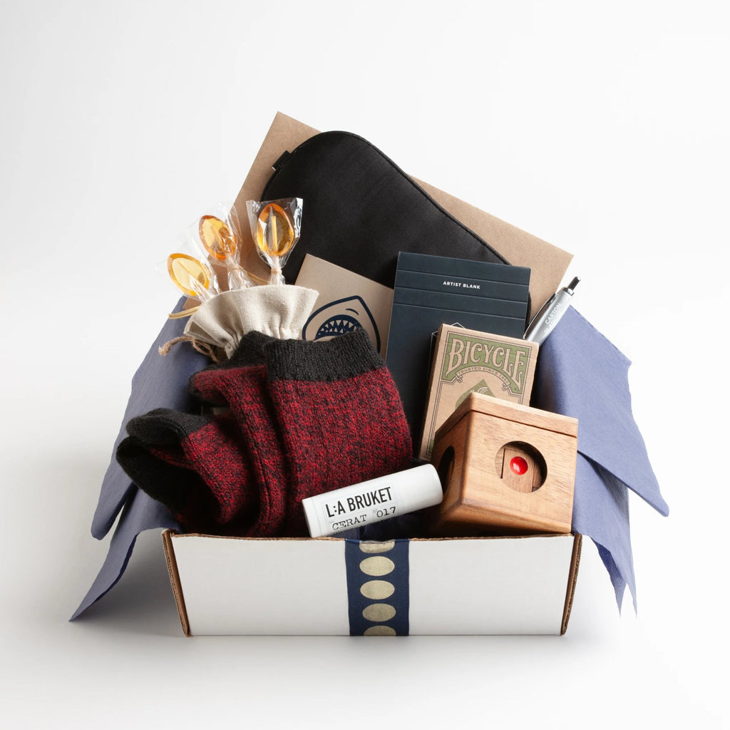 Carton Rouge - a bevy of mens get well essentials. Carton includes : warm but rugged alpaca socks, moisturizing lip balm, silk eye mask, captivating wooden game, eco-friendly playing cards.