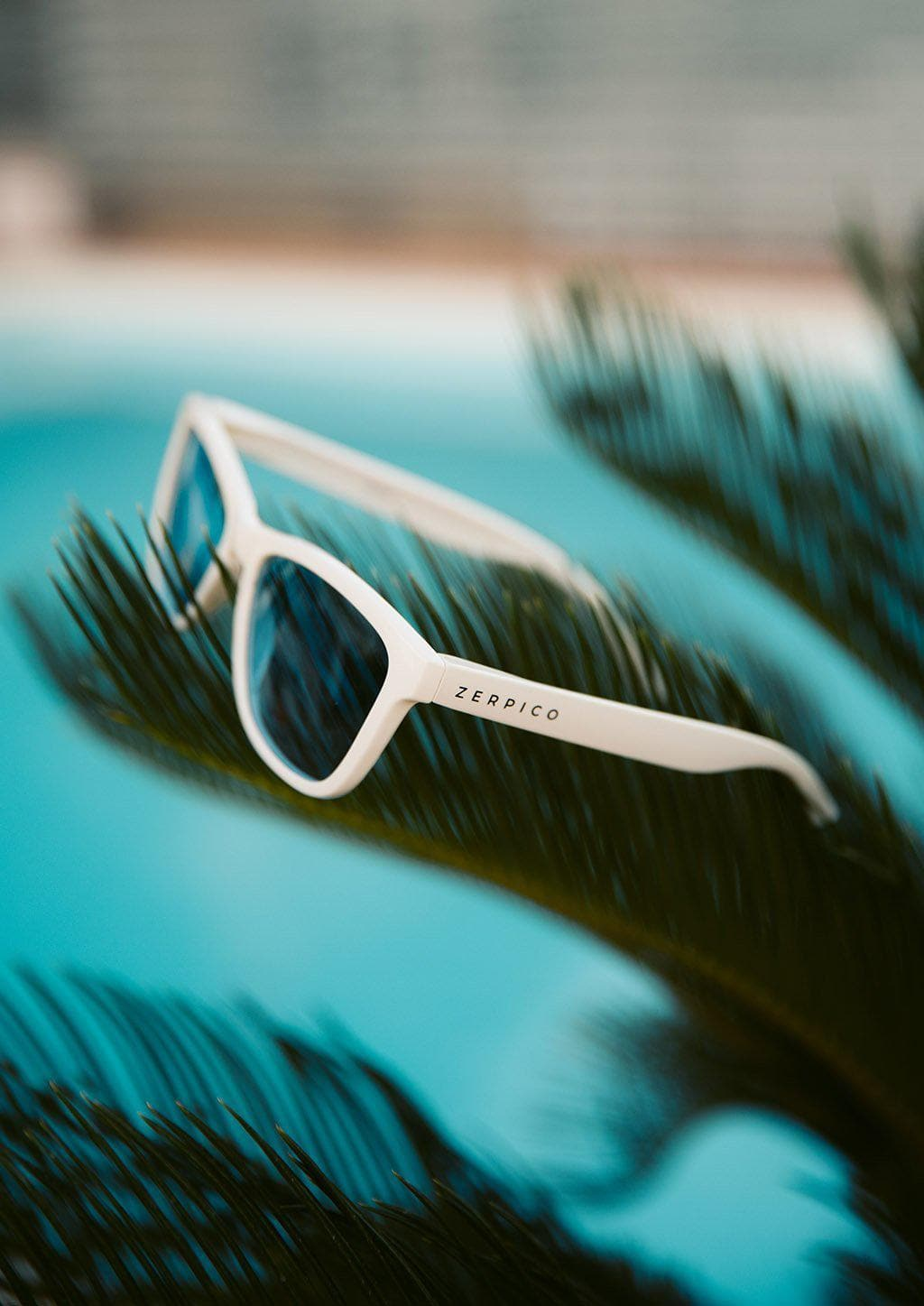 Our Mood V2 is an improved version of our last wayfarers. Plastic body for great quality and durabilty. This is Ace with white frame and black lenses. Lifestyle photo outside beside a pool.