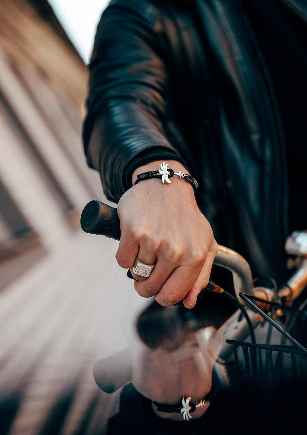 Starlight - Season two Palm anchor bracelet with black leather. On male model riding a motorcycle.