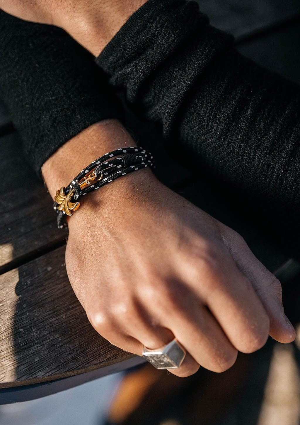 Trophy - Triple - Season two Palm anchor bracelet with black and white nylon band. With black sweater.