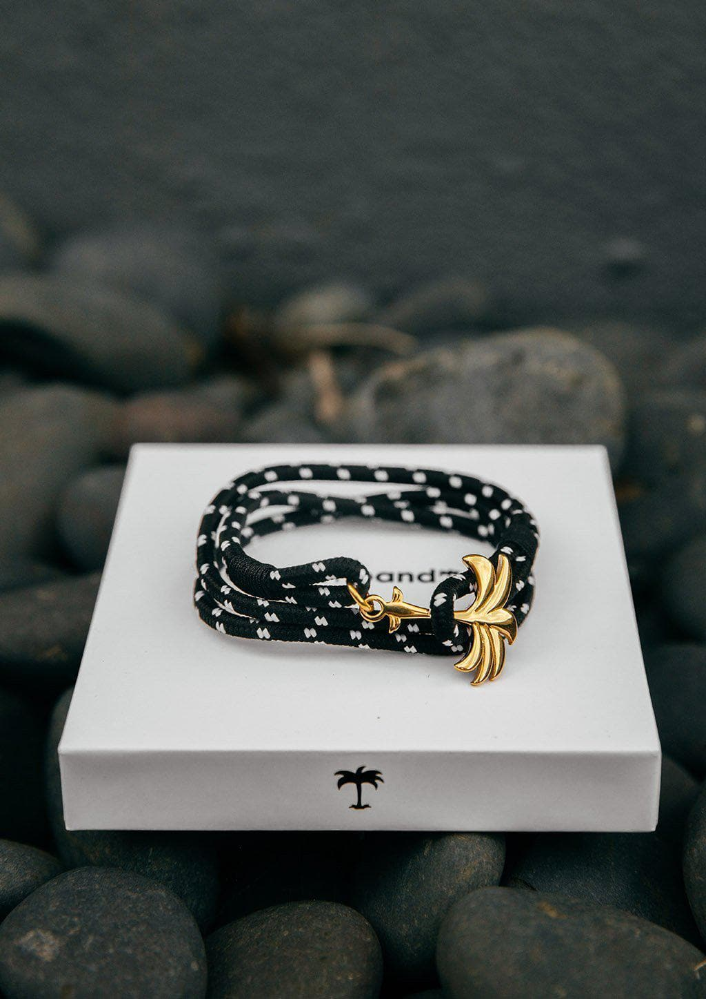 Trophy - Triple - Season two Palm anchor bracelet with black and white nylon band. Close up on box.