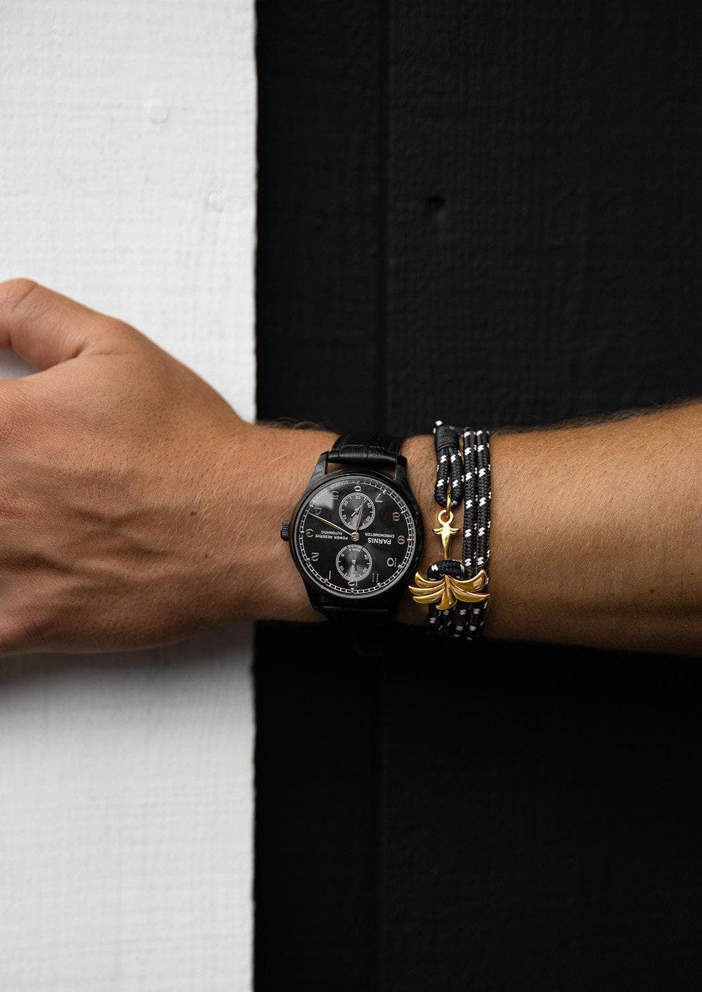 Trophy - Triple - Season two Palm anchor bracelet with black and white nylon band. Black and white wall.