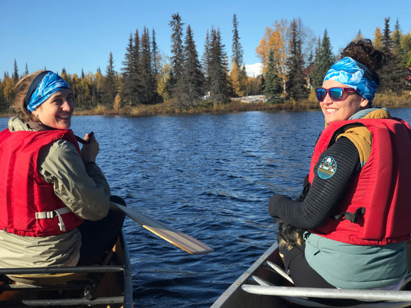 Sarah and Katrina canoeing side by side in matching Turnagain Pass buffs