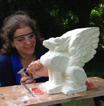 Lucy Cortese wearing googles and holding a chisel and hammer, hand carving a stone griffin sculpture