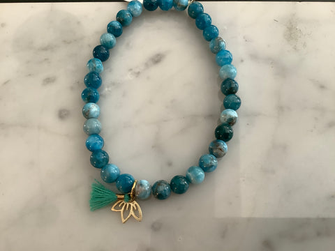 Blue apatite beaded bracelet with gold vermeil lotus charm and mini green tassel