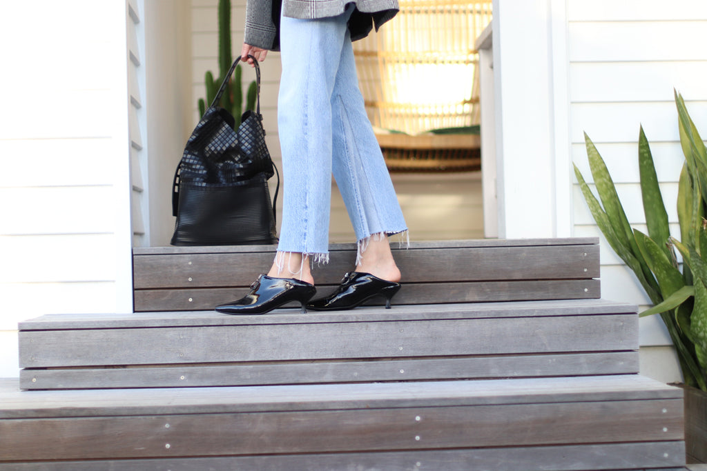 Marilee Pham in her EOD Elle kitten heel pumps with back heel down for a casual weekend look on top of the stairs