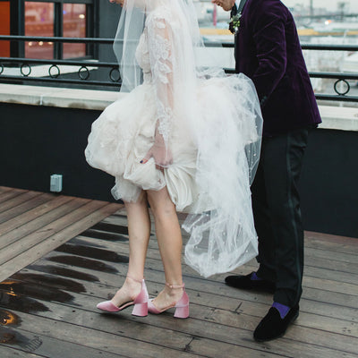 A bride wearing ASHLEY LIM Scarlett pink velvet shoes on her wedding day