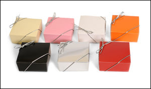 photo of seven paper boxes in seven different colors containing luscious Laura's Brownies