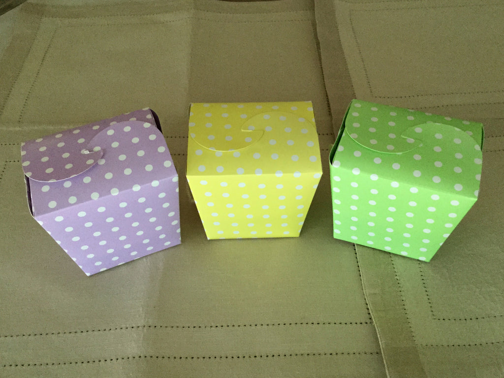 photo of group of three colorful paper quart boxes in purple, yellow, and green with white polka dots containing delicious Caramel Brownies