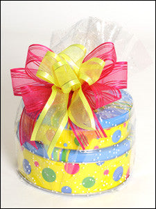 photo of two stacked colorfully decorated round tins wrapped in cellophane tied with bows containing delicious Laura's Brownies