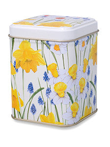 photo of colorfully decorated tall square tin painted white with bright yellow and cornflower blue flowers and containing delicious Laura's Brownies