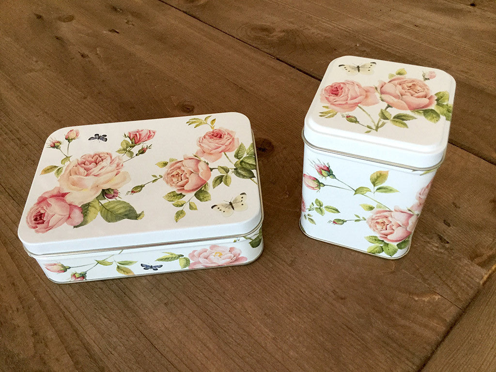photo of two colorful painted tin boxes, one rectangular, one a tall square, with pattern of pink roses and containing delicious goodies from Laura's Brownies