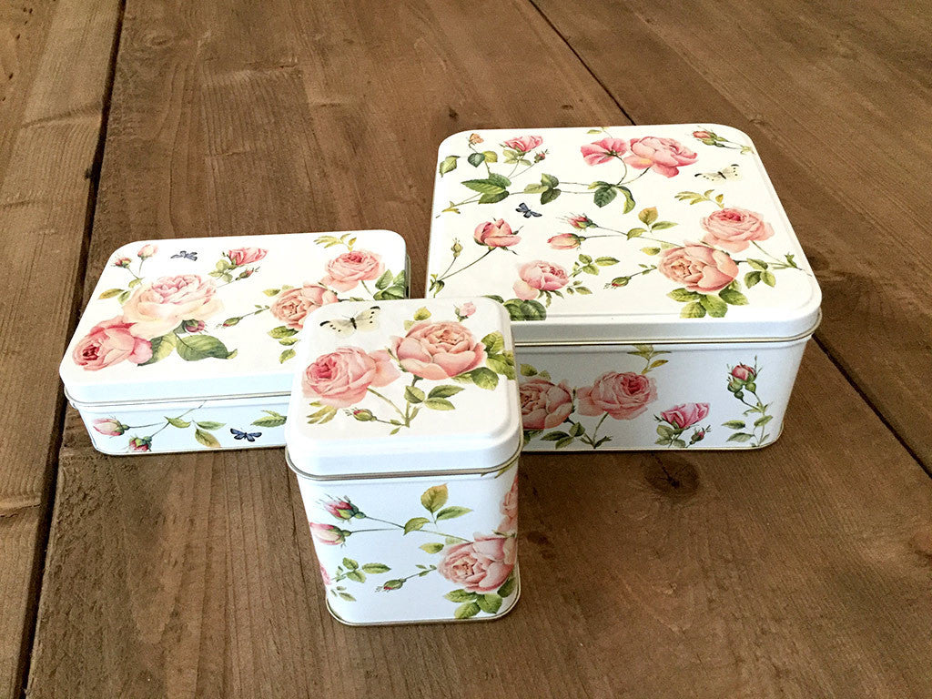photo of three colorful painted tin boxes, one medium square, one small rectangular, one small tall square, with pattern of pink roses and containing delicious goodies from Laura's Brownies