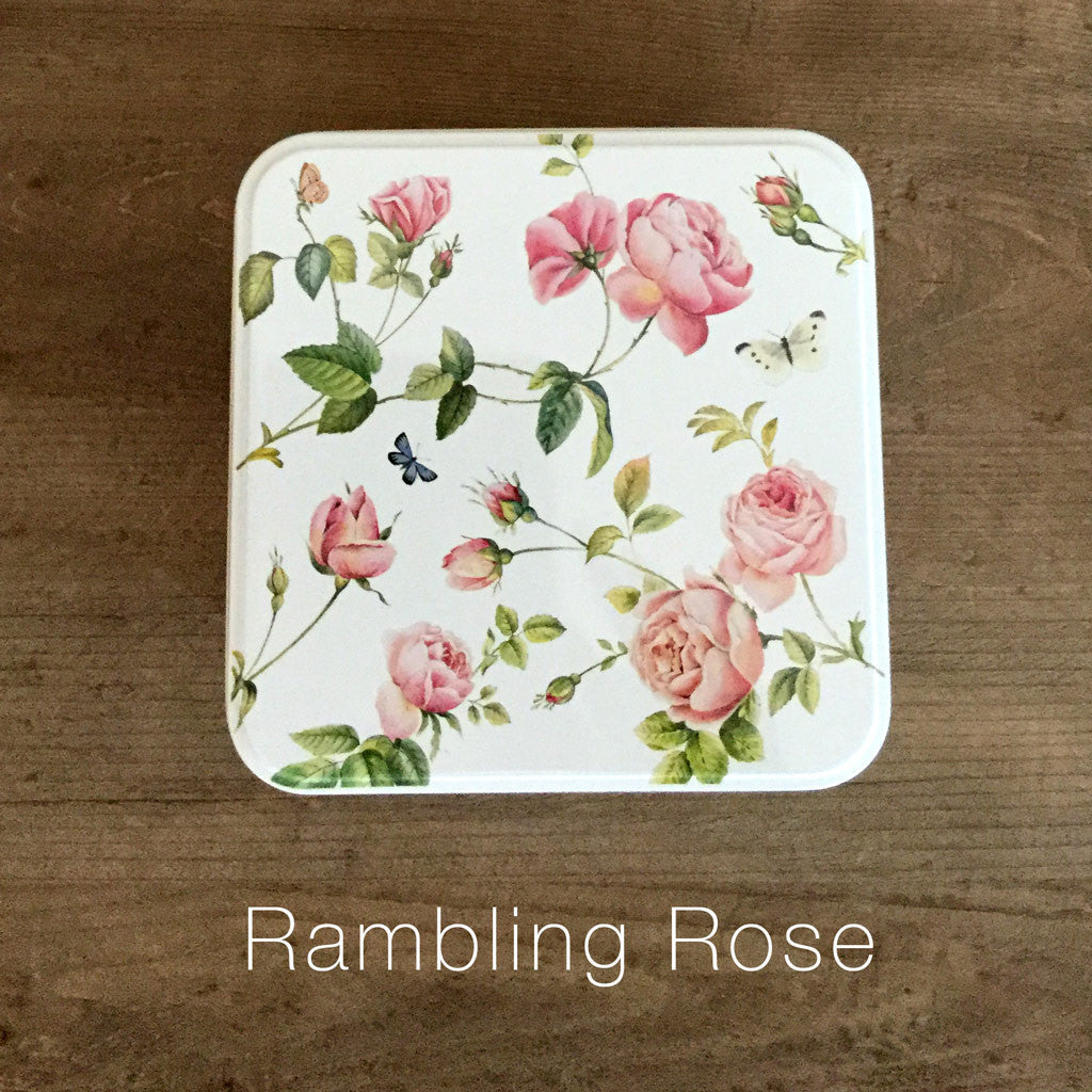 photo of colorfully painted square tin featuring an illustrated pink roses and containing delicious Laura's Brownies