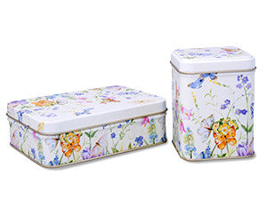 photo of two colorful painted tin boxes, one rectangular, one a tall square, with pattern of flower blossoms and butterflies and containing delicious goodies from Laura's Brownies