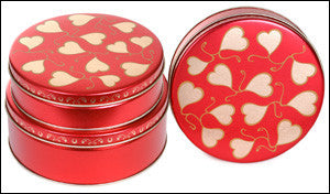 photo of three solid red tins each with gold illustrated Valentine's Day hearts and filled with delicious Laura's Brownies