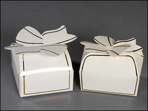 photo of two small white rounded-top paper cube party favors with integral paper bows containing Laura's Brownies