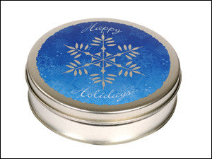 photo of round red tin with Happy Holidays text and a large illustrated snowflake painted on its lid and containing delightful Laura's Brownies