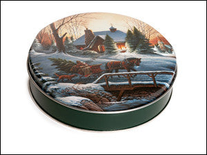 photo of round green tin with wintery scene of horseback sleigh past a snowbound home painted on its lid and containing delightful Laura's Brownies