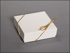 photo of white cardboard box wrapped with gold string and bow containing delicious Laura's Brownies