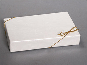 photo of rectangular shallow white cardboard box wrapped with gold string and bow containing delicious Laura's Brownies