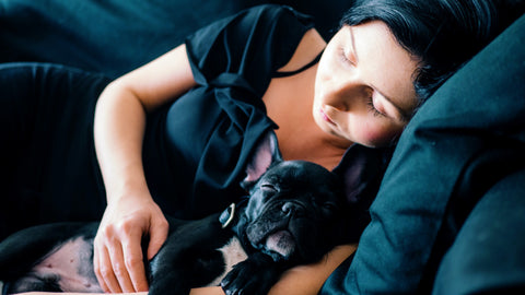 A dog and a lady are sleeping togther on a couch