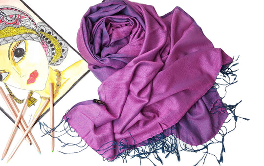 This Pashmina scarf is inspired by the colours of pink lotus flowers. It has the traditional lozenge patterns woven intricately into it. This pashmina scarf has been blend with 30% silk to give it a beautiful shiny appearance. This shawl can be worn on both sides pink or lavendar. Our scarves are created using natural fibers. This scarf can be wrapped around like a blanket scarf. It has hand tied tassles on both sides.