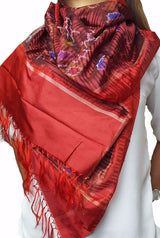 This is luxurious red scarf is a pure silk Ikkat scarf. It has tassels at two borders that are hand tied to adorn your scarf.  Ikkat is a design wherein the yarns are first dyed using resist dyeing technique and then woven into beautiful patterns.  The Characteristic of this style is that there is apparent blurriness in the designs as the weaver faces a lot of difficulty aligning the already dyed threads to create patterns. Ikkat is prevalent mostly in Gujrat, Odisha and Andhra Pradesh in India.  This scarf