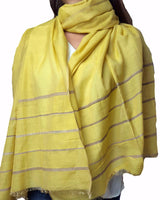 This Yellow tussar Silk scarf with elementary grey horizontal stripes woven into it provides it an uncomplicated look. This unpretentious scarf will make you look elegant without appearing fussy. An easy to carry design, this scarf is made of tussar silk. The edges of the scarf has fringes emerging from the ends of the woven threads.  This scarf can be wrapped around an evening shawl around an elegant cocktail dress.   Tussar is another variety of silk produced from the cocoon of a wide winged moth known as